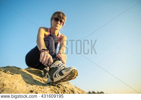 Woman Hiker Tying Shoe Laces Of Her Sport Boots While Climbing Steep Big Rock On A Sunny Day. Young