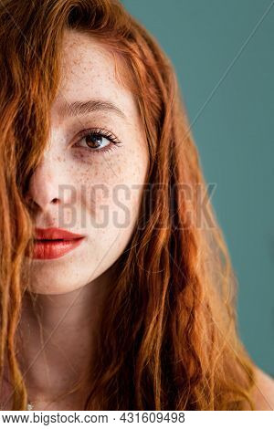 Face Of A Beautiful Woman With Red Hair And Lips Isolated On Green Background. High Quality Photo