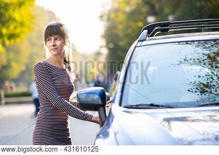 Young Female Driver Resting Near Her Car Enjoying Warm Summer Day. Travel And Getaway Concept.