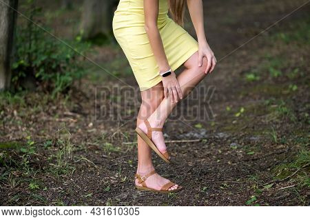 Woman In Pink Dress Holding Her Knee With Hands Having Cramp Pain.