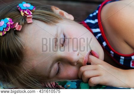Portrait Of Sleeping Pretty Child Girl Who Sucks Her Finger While Sleeping. Children Healthcare And