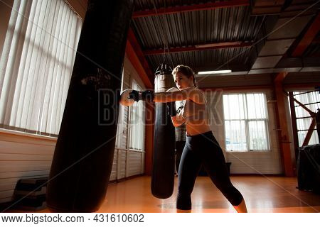 Young Woman Doing Boxing Workout In The Gym, She Is Wearing Boxing Gloves And Punching A Punching Ba