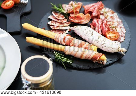 The Sausage Slices Are Beautifully Laid Out On The Plate. Meat Delicacies Decorated With Herbs And V