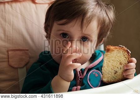 1 Year Old Baby Old Baby Girl Eats Panettone. Cute Little Caucasian Girl Holding Easter Cake.