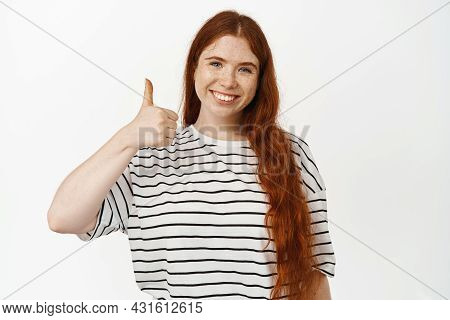 Yes. Smiling Redhead Female Model Showing Thumbs Up. Girl With Red Long Hairstyle And Freckles Likes
