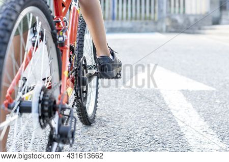 Close Up Of A Childs Legs Mounted On His Bicycle Ready To Start Riding Next To A White Arrow Sign Pa