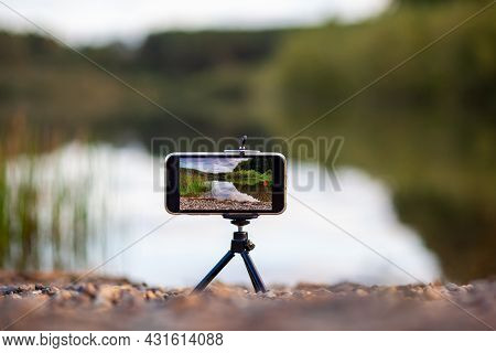 A Close Up Of The Phone On A Tripod Takes A Video Or A Photo Of Nature. A Beautiful Lake In The Fore