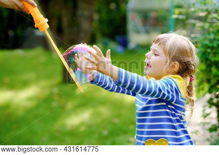 Happy Little Blonde Preschool Girl Having Fun With Blowing Soap Bubble Blower. Cute Child Playing On