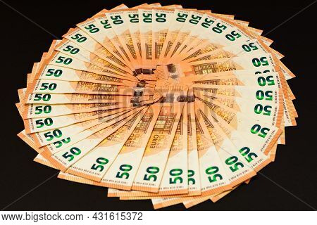 Pile Of 50 Real Euro Banknotes Isolated On A Black Background.