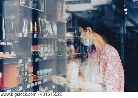 Woman In Protective Mask Shopping In Beauty And Make Up Store Shot Through Window