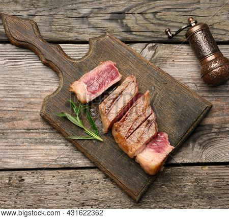 Sliced Fried Beef Steak New York Striploin On A Wooden Cutting Board, Degree Of Doneness Rare, Top V