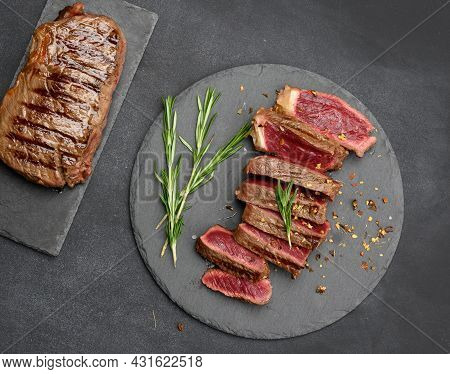 Fried Beef Steaks Cut Into Pieces On A Black Board, The Degree Of Doneness Rare With Blood, Top View