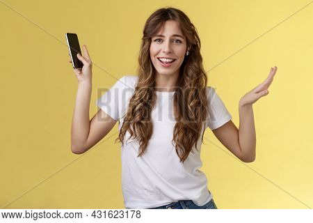 Carefree Good-looking Lively Sociable Curly-haired Girl Having Fun Wearing Wireless Earbuds Dancing