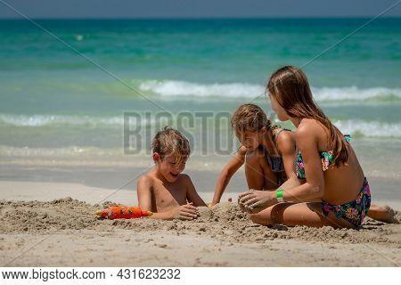 Three Cheerful Kids Playing on the Sea Shore. Happy Siblings Playing wth Sand. Big Family Enjoying Summer Holidays on the Beach