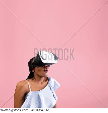 Cyberspace. Shocked African American Woman Wearing Vr Helmet, Experiencing Virtual Reality On Pink B
