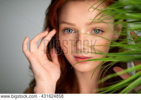 Ginger-haired Young Woman Touching Red Hair Posing With Plant, Studio