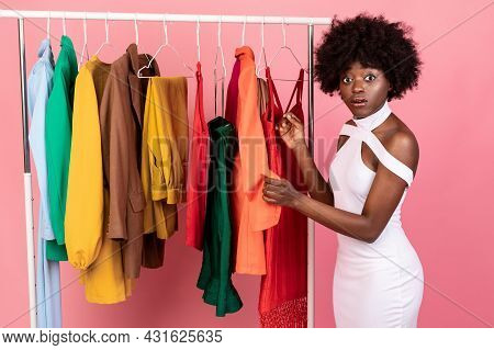 Puzzled Black Female Shopping Having Difficulties Choosing Clothes, Pink Background