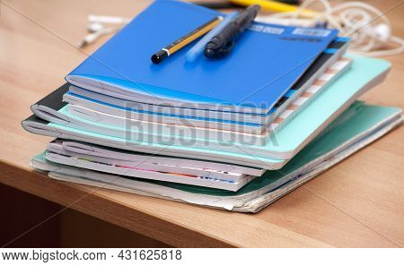 Notebooks In Blue, Pink And Other Colors, Pens And Pencils And Other Office Supplies On A Wooden Des