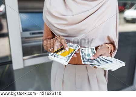 Unrecognizable Millennial Arabian Lady In Hijab Hold A Lot Of Dollars And Credit Card, Withdrawing M