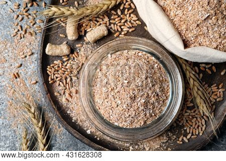 Jar And Sack With Wheat Bran On Grey Table, Flat Lay