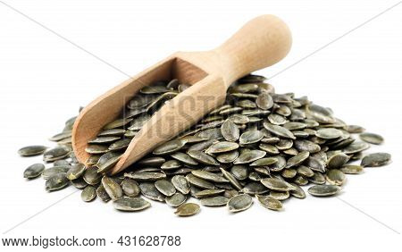 Heap Of Pumpkin Seeds And A Wooden Scoop Close-up On A White Background. Isolated