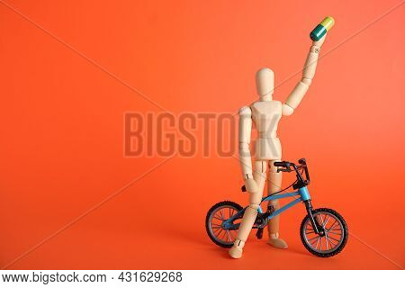 Sportsman With Pill And Bike Model On Red Background, Space For Text. Using Doping In Cycling Sport