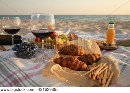 Blanket With Wine, Juice And Snacks For Picnic On Sandy Beach