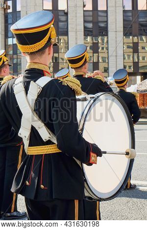 Musician Dressed In Black Parade Uniform  With Yellow-red Chevrons And Golden Fringe Epaulets Playin