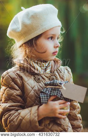 Little Girl Holds Glass Jar Filled With Yellow And Green Leaves, Berries And Seeds With Empty Paper