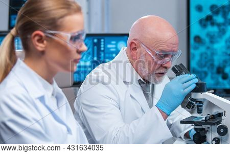 Professor and doctor work in a modern scientific laboratory using equipment and computertechnologies. Group of scientists make research and develop new vaccines. Science and healthcare concept.