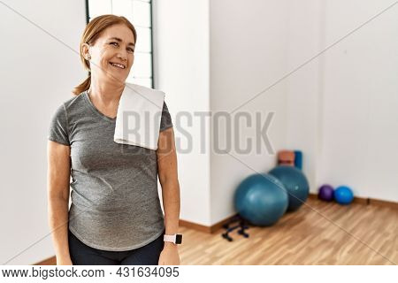 Middle age woman wearing sporty look training at the gym room looking away to side with smile on face, natural expression. laughing confident.