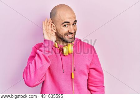 Young bald man wearing gym clothes and using headphones smiling with hand over ear listening an hearing to rumor or gossip. deafness concept.