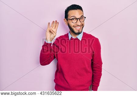 Hispanic man with beard wearing business shirt and glasses waiving saying hello happy and smiling, friendly welcome gesture