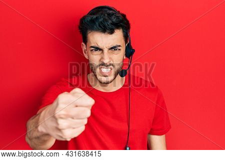 Young hispanic man wearing call center agent headset annoyed and frustrated shouting with anger, yelling crazy with anger and hand raised