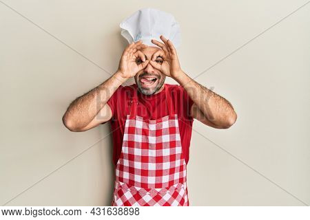 Young hispanic man wearing baker uniform doing ok gesture like binoculars sticking tongue out, eyes looking through fingers. crazy expression.
