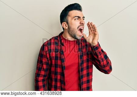 Young hispanic man wearing casual clothes shouting and screaming loud to side with hand on mouth. communication concept.