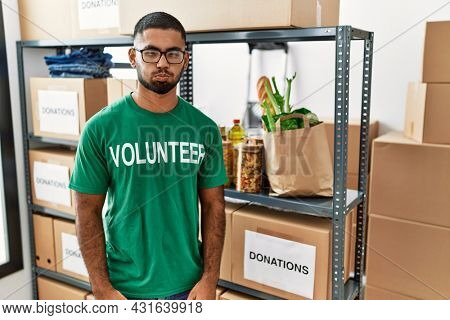 Young indian man volunteer holding donations box puffing cheeks with funny face. mouth inflated with air, crazy expression.