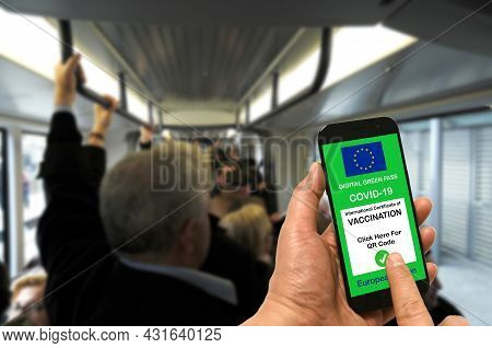 A Man On A Tramway Is Holding A Smartphone With The European Union Digital Green Pass For Covid-19.