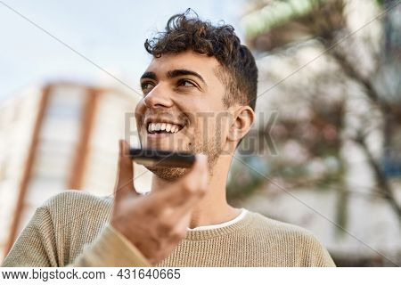 Young hispanic man sending voice message using smartphone at the city