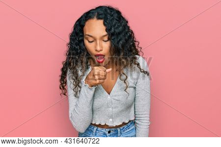Young hispanic woman with curly hair wearing casual clothes feeling unwell and coughing as symptom for cold or bronchitis. health care concept.