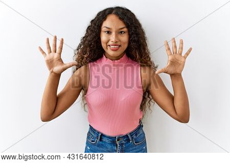 Beautiful hispanic woman standing over isolated background showing and pointing up with fingers number ten while smiling confident and happy.
