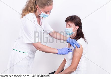 Female Doctor Or Nurse Giving Shot Or Vaccine To Patients Shoulder. Vaccination And Prevention Again