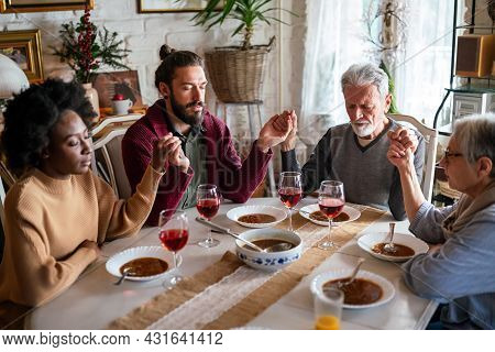 Family And Religious Concept. Group Of Multiethnic People With Food Praying Before Meal
