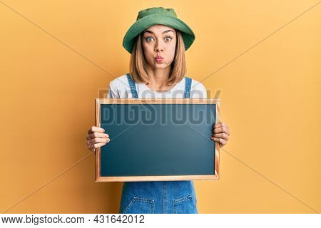 Young caucasian blonde woman holding blackboard puffing cheeks with funny face. mouth inflated with air, catching air.