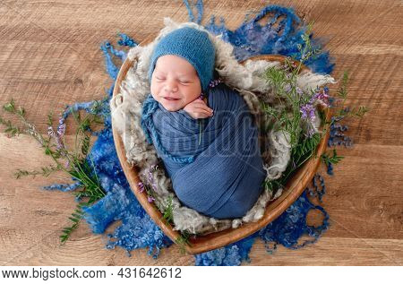Adorable newborn baby boy swaddled in blue fabric holding lavander flower in his hands and smiling during sleeping. Cute infant kid napping in fur in wooden heart bed during studio photoshoot.