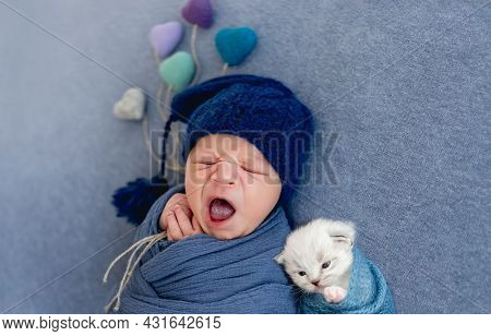 Newborn baby boy swaddled in blue fabric and wearing hat sleeping with small fluffy white kitten and holding knitted toy hearts. Portrait of yawning infant kid with little cat