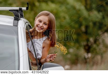 Preteen girl looking from car window and smiling. Cute child kid during journey in vihicle at nature