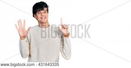 Handsome hipster young man wearing casual winter sweater showing and pointing up with fingers number seven while smiling confident and happy.
