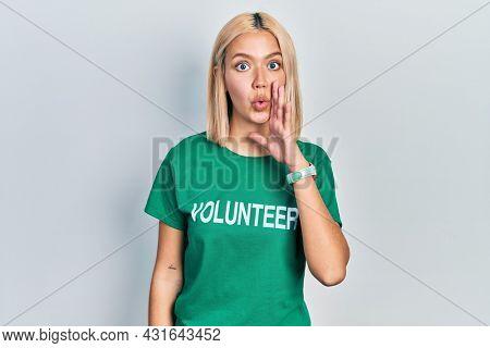 Beautiful blonde woman wearing volunteer t shirt hand on mouth telling secret rumor, whispering malicious talk conversation