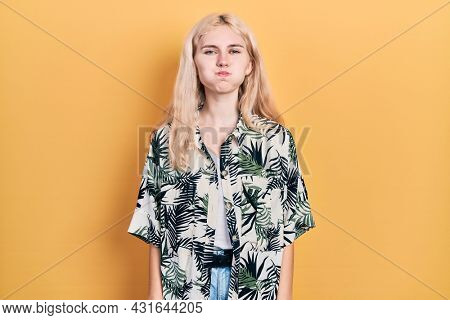 Beautiful caucasian woman with blond hair wearing tropical shirt puffing cheeks with funny face. mouth inflated with air, crazy expression.